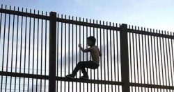 A young man climbs the border fence near Brownsville, Texas.